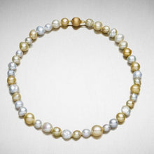 A BUNDA 'Strand' of baroque shaped Cultured South Sea pearls of clean skin and excellent lustre, white, champagne and golden in colour, strung knotted with a round, box style clasp in 18 carat yellow gold.  Dimensions of pearls: 9.0 - 12.0mm  Total length: 46cm.