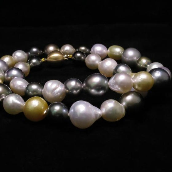 A BUNDA strand of baroque shaped Cultured South Sea and Tahitian pearls, strung knotted with an 18 carat yellow gold clasp. The 39 pearls range in size from 9.2mm up to 12.8mm, feature colours of green, white and gold and have a clean skin and an excellent lustre.  Total length: 45.0cm.  Total weight: 63.79g