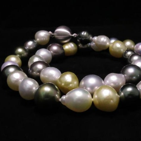A BUNDA strand of baroque shaped Cultured South Sea and Tahitian pearls, strung knotted with an 18 carat white gold clasp. The 39 pearls range in size from 8.70mm up to 13.00mm, feature colours of green, white and gold and have a clean skin and an excellent lustre.  Total length: 45.0cm.  Total weight: 67.70g