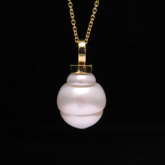 A BUNDA Cultured South Sea pearl 'Eva' pendant in 18 carat yellow gold, featuring a circle drop shaped pearl with a clean skin and an excellent lustre, white in colour with pink overtones, fitted with an 18 carat yellow gold Trace chain.  Dimensions of pearl: = 15.00 - 18.40mm  Total weight: 9.42g