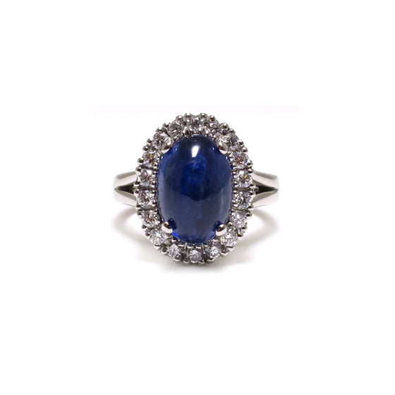 A BUNDA 'Valentin' Kyanite and diamond ring in platinum, featuring a cabochon cut Kyanite, surrounded with castle set round brilliant cut diamonds to the head. The band of the ring features a split shank.  Weight of Kyanite: 1 = 7.00ct. Origin: Kashmir.  Characteristics of additional diamonds: 18 = 0.54ct, F colour, VS clarity.  Total weight of Ring: 13.29 grams.