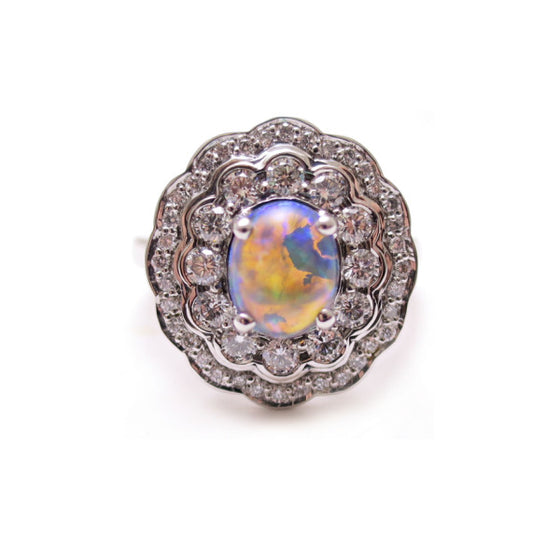 A BUNDA 'Tanara' opal and diamond ring in 18ct white gold, featuring a cabochon cut black opal, claw set to the centre and surrounded with two rows of round brilliant cut diamonds, bead and bezel set.  The Black opal weighs 1.39ct and features colours predominately of blue and green. Origin: Andamooka, Australia.  There are 48 diamonds = 0.70ct, F colour and VS clarity.  Total weight of Ring: 7.51 grams