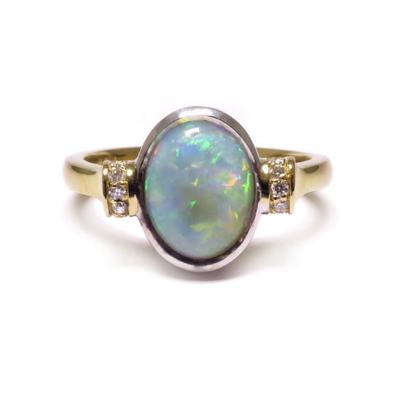 A BUNDA 'Dorado' White Opal and diamond ring in 18ct yellow and white gold, featuring an oval cut White Opal, with round brilliant cut diamonds threadset along the top of each shoulder.  Characteristics of White Opal: 1 = 1.15ct, featuring colours of blue, green and red.  Characteristics of diamonds: 10 = 0.05ct, F colour, VS clarity.  Total weight: 4.84grams