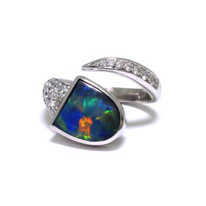 A Superb Australian Black Opal, with excellent play of colour, bezel set in 18ct white gold with pave and thread set diamonds in a wrap setting.  The Opal weighs 1.56ct, features colours of blue, green and strong reds and originates from Lightning Ridge, Australia.  Characteristics of additional diamonds: 20 = 0.68ct, F colour, VS clarity.  Total weight of Ring: 8.80 grams