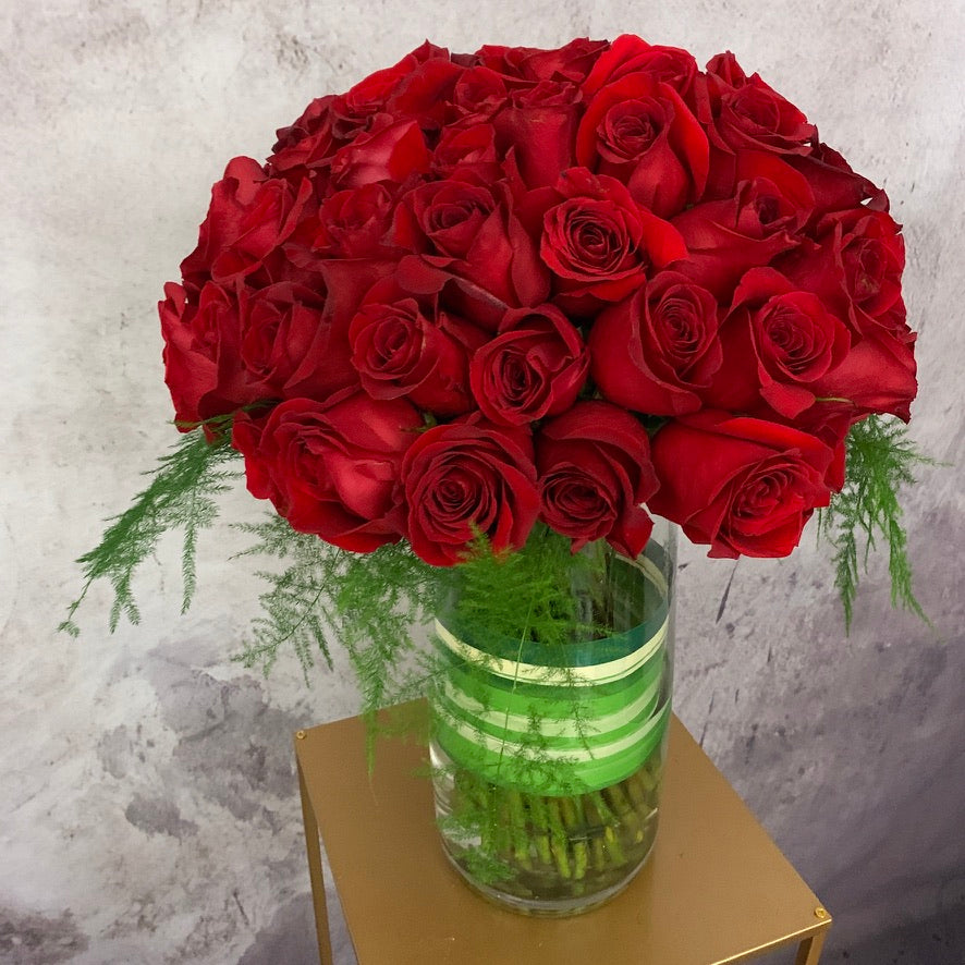 Bouquet of red roses arranged in a vase with greenery - Petalino Flower Bar & Events