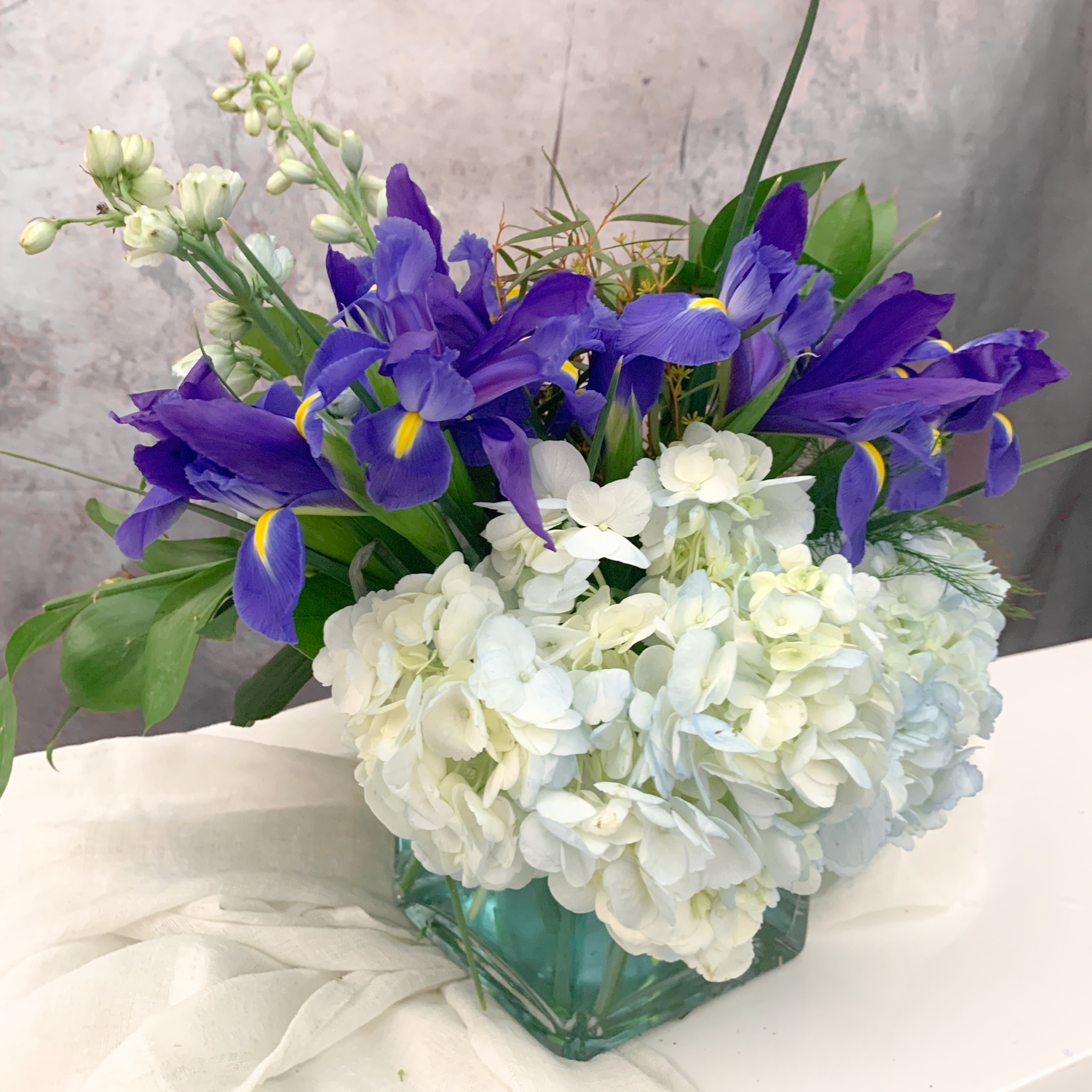 Blue flowers arranged in a square glass vase with tinted blue water - Petalino Flower Bar