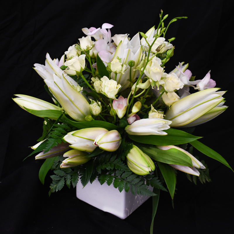 Spray roses and lilies in a small white pot by Petalino flower bar & events
