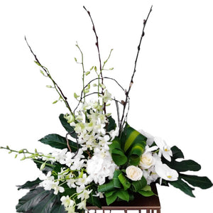 White & Green flowers arranged in a tray includes large Tropical leaves with Orchids, Hydrangeas, Roses by Petalino Flower Bar & Events