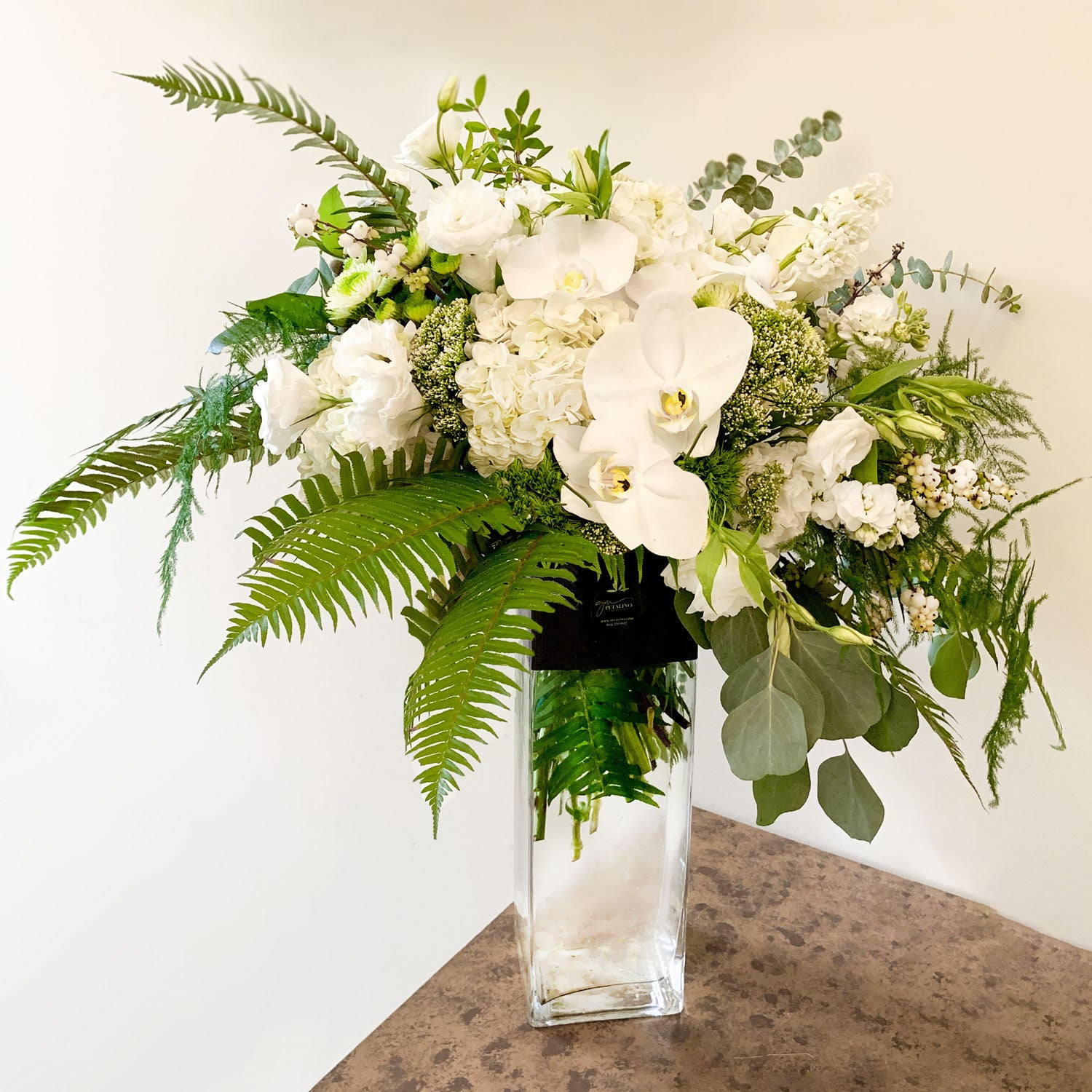 Large all white vase arrangement in tall glass with orchids and tree fern garden look - Petalino Flower Bar & Events