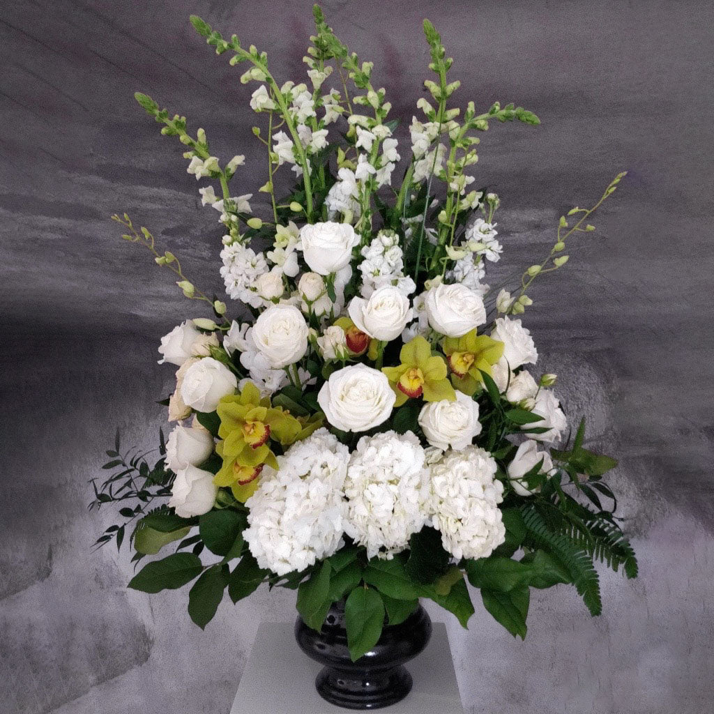 Roses and green orchids with 3 hydrangeas floral arrangement in a black urn container