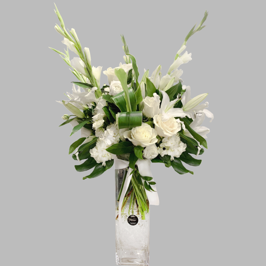 White and green vase arrangement with roses, hydrangeas and glad and large monstera leaves arrangenged in a tall vase with lilies. modern look | delivery by Petalino Flower Bar and Events