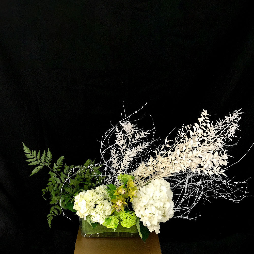 "Christmas centerpiece, white and green colours hydrangeas and preserved Italian ruscus leaves and white branches arranged in a 12""W Glass vase."