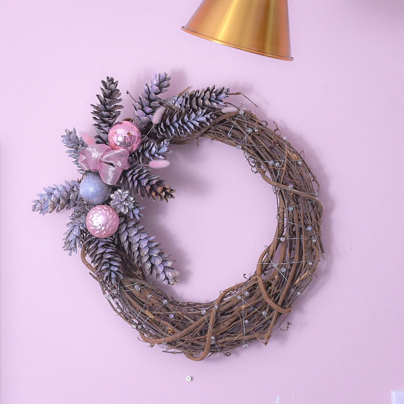Christmas wreath with vine woody material decorated with metallic pastel pink and white painted pine cones wrapped in white pearl wire.