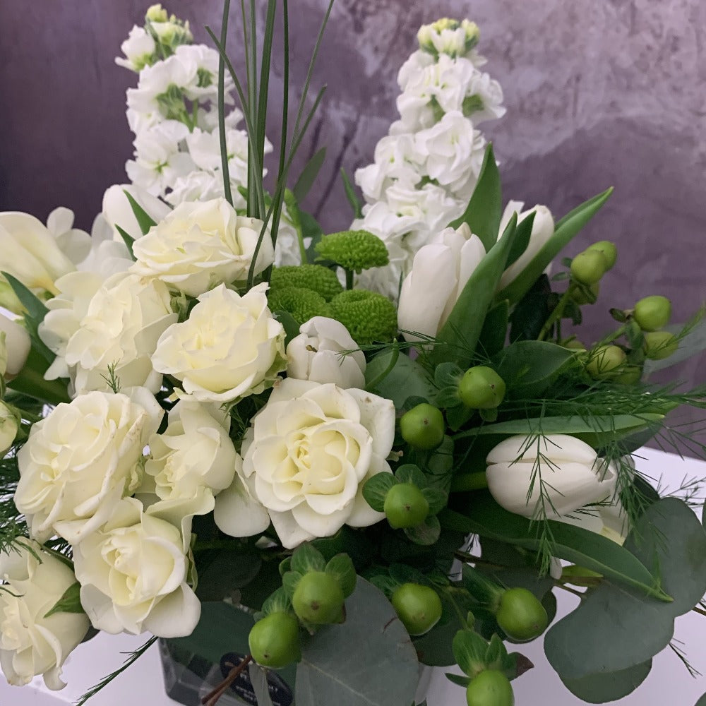 white flowers stock spray roses tulip arrangemd in a rectangle square glass vase- Petalino Flower Bar