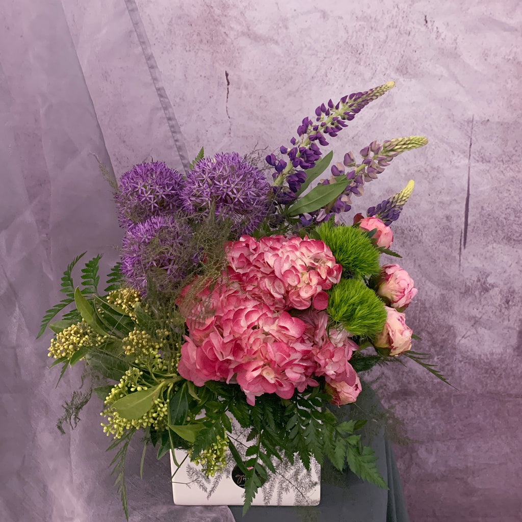 Pink and Purple peonies and hydrangeas and allium flowers arranged in a white square vase by Petalino Flower Bar and Events