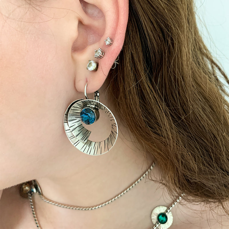 spiral form hammered silver earrings with Montana blue crystals