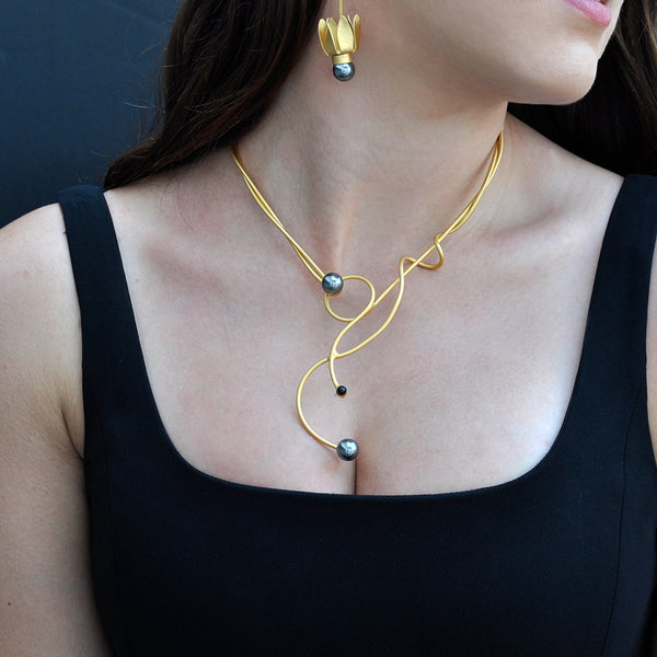 gold sculptural necklace with black pearl