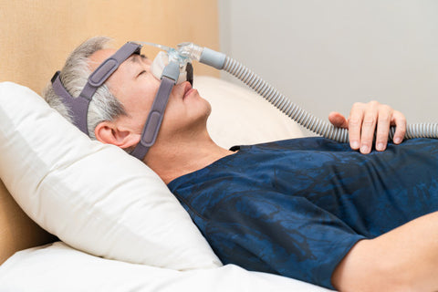 middle aged man wearing CPAP mask