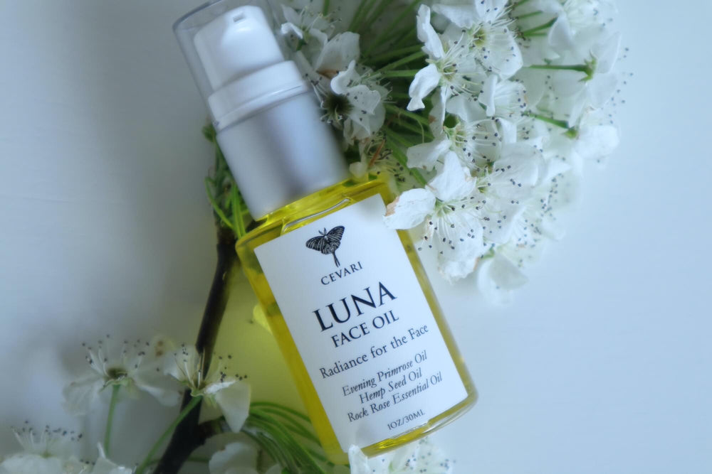 Luna Face Oil Laying On Tree Branch with Flowers