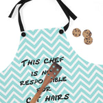striped cat lover apron with black straps next to cookies and a wooden spatula