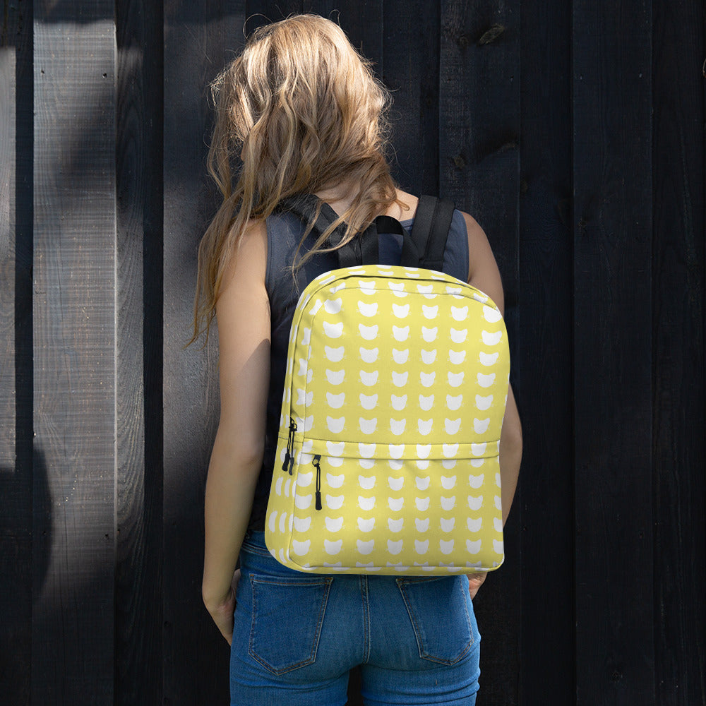 woman wearing yellow and white cat heads pattern backpack