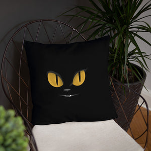 black cat yellow eyes on black throw pillow on chair