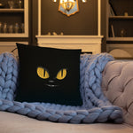 black cat with yellow eyes design on black throw pillow on quilt