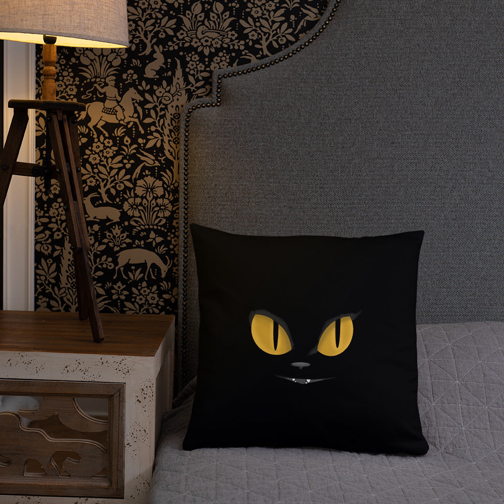 black cat yellow eyes on black throw pillow on the bed