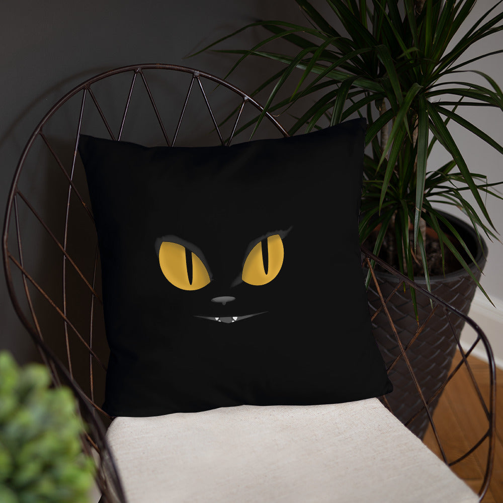 black cat yellow eyes on black throw pillow on pale chair