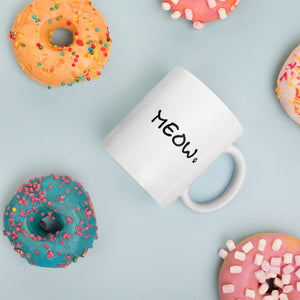 white mug with simple Meow text next to donuts