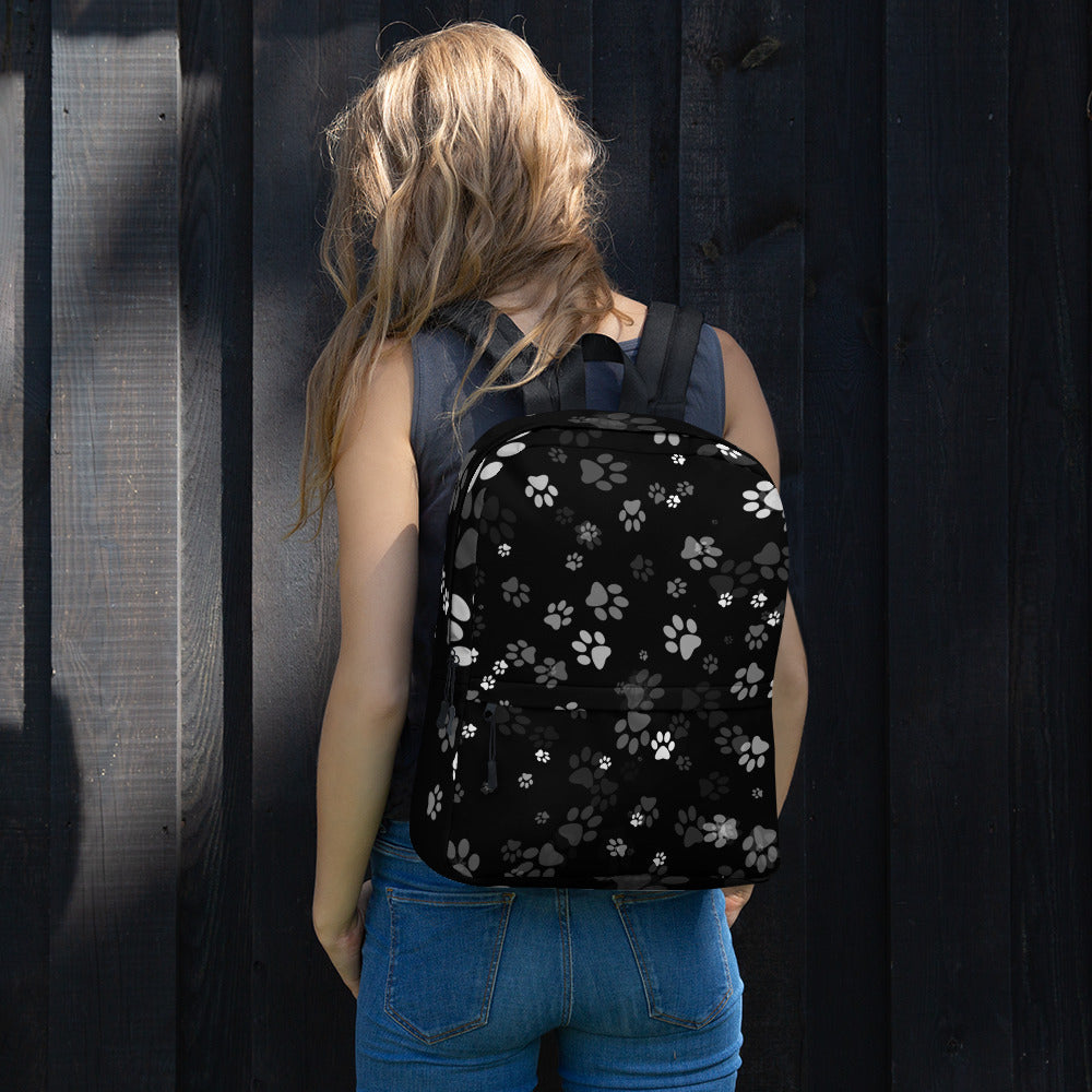 girl wearing black backpack with cat paw prints