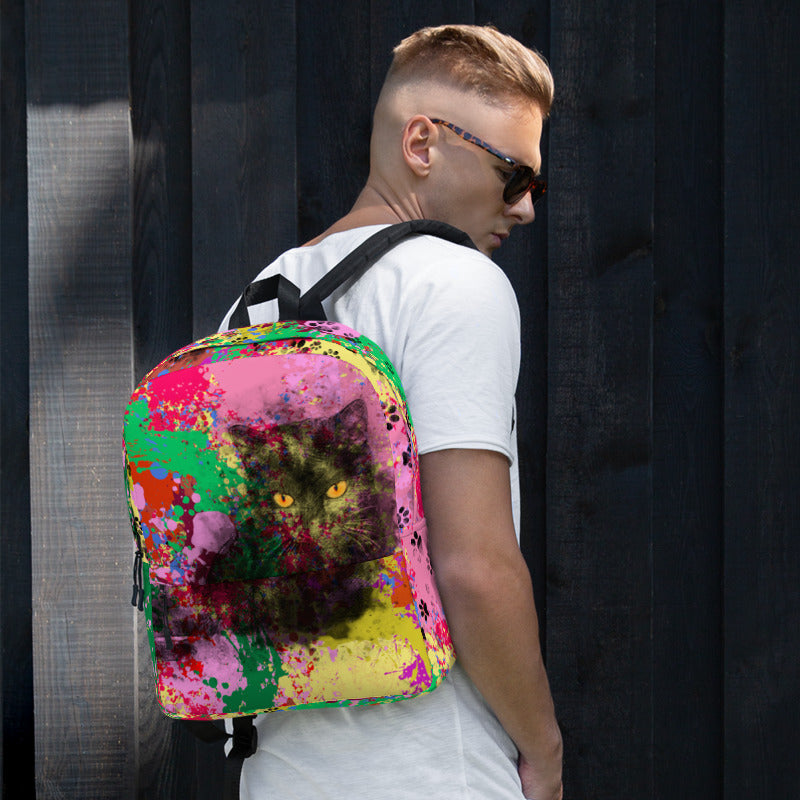 Guy wearing backpack with black cat on colorful splattered background design