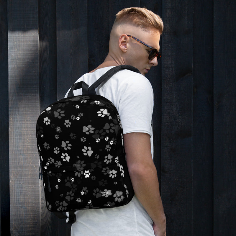 guy wearing black backpack with cat paw prints