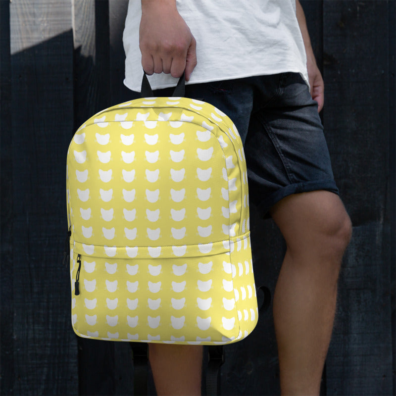 man holding a white and yellow cat head pattern backpack