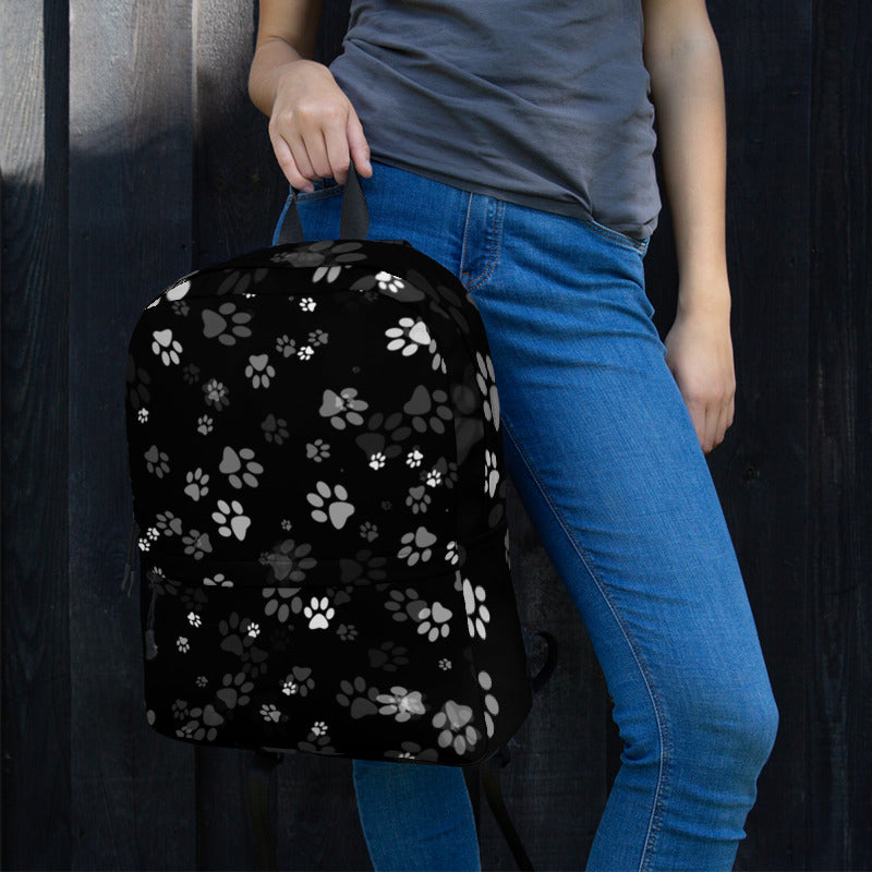 girl holding black backpack with cat paw prints