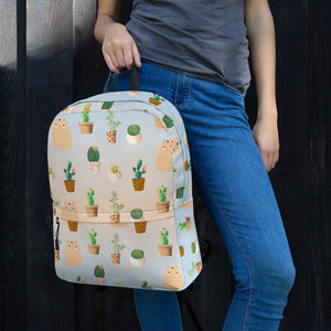 woman holding cactus and cat pattern backpack