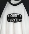 • Unisex Modern Baseball T-Shirt • County Brand 1792 Prince Edward County • White w/ Black Heather Sleeves