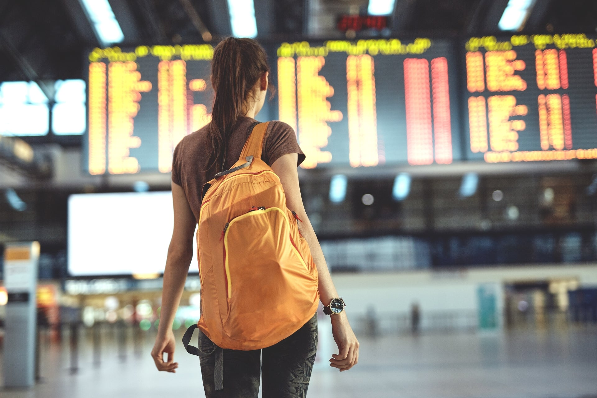 A woman with an orange back pack stands inside an airport wondering can you take a pipe on a plane?