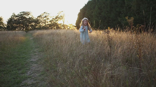little girl dancing and skipping through meadow with sunset in the background wearing a flower crown wearing her glitter sparkle handmade jersey dress party disco occasion dress inspired frozen elsa sustainable