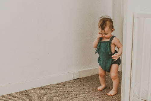 girl walking into a room rubbing her eye wearing the forest green bohemian handmade summer romper with adjustable straps easy to layer up hippy sustainable baby toddler clothing