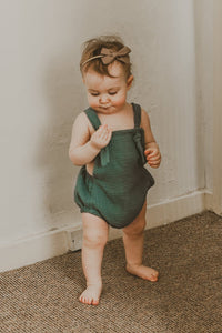 girl walking into a room wearing the forest green bohemian handmade summer romper with adjustable straps easy to layer up hippy sustainable baby toddler clothing