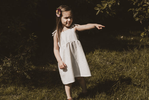 girl stood in garden in summer wearing a cotton linen dress in white adjustable straps sustainable bohemian hippy beach clothing