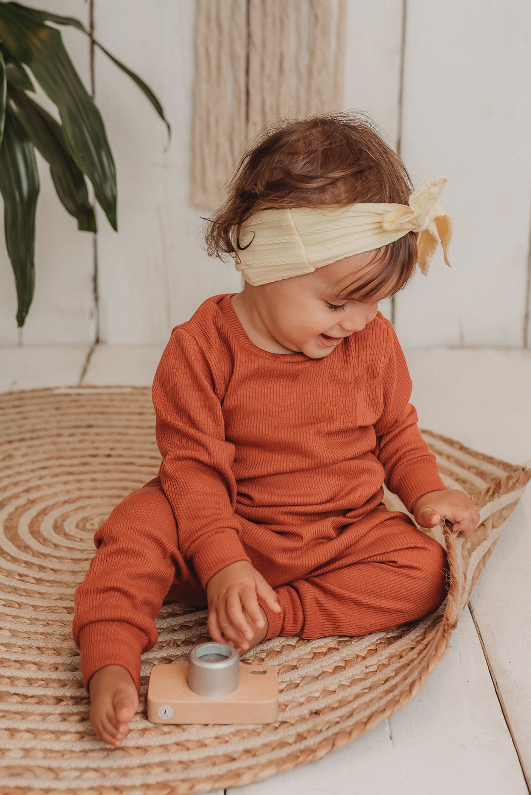toddler girl sits on boho hippy mat with her handmade lounge comfy set cosy in rust orange leggings lounge jumper sustainable unisex