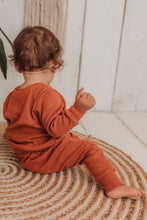 Load image into Gallery viewer, baby girl sits on boho hippy mat with her handmade lounge comfy set cosy in rust orange leggings lounge jumper sustainable unisex
