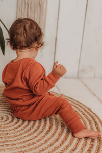 baby girl sits on boho hippy mat with her handmade lounge comfy set cosy in rust orange leggings lounge jumper sustainable unisex