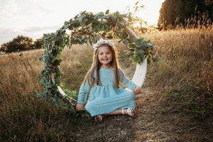 little girl sat in flower arch in a bohemain meadow with sunset in the background wearing a flower crown wearing her glitter sparkle handmade jersey dress party disco occasion dress inspired frozen elsa sustainable