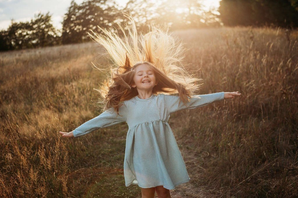 girl flicking her hair back whilst wearing a glitter sparkle party occasion dress in a meadow with the sunset in the background dress inspired by frozen elsa handmade sustainable ethically clothing