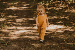 toddler boy walking through a forest in a handmade orange romper with adjustable straps with curly hair bohemian style eco friendly sustainable clothing