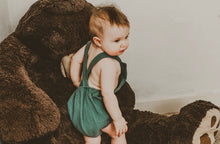 Load image into Gallery viewer, girl playing with teddy bear wearing the unisex forest green bohemian handmade summer romper with adjustable straps easy to layer up hippy sustainable baby toddler clothing