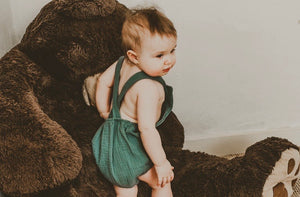 girl playing with teddy bear wearing the unisex forest green bohemian handmade summer romper with adjustable straps easy to layer up hippy sustainable baby toddler clothing